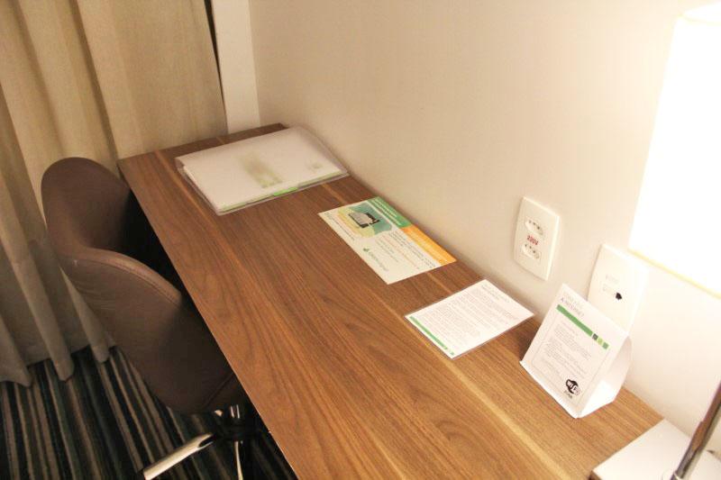 Mesa de trabalho ampla e várias tomadas.