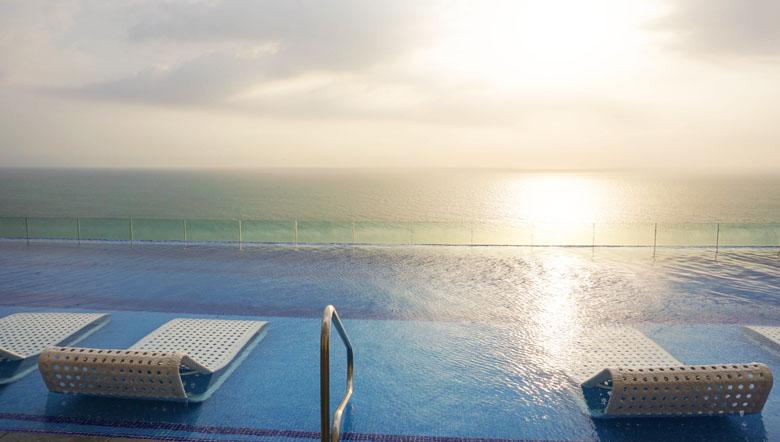Que tal relaxar em uma espreguiçadeira dentro da piscina para assistir ao pôr do sol?