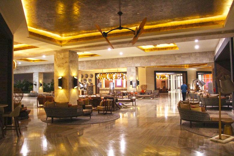O lobby é arrojado e no seu entorno há restaurantes, lojas e o casino.