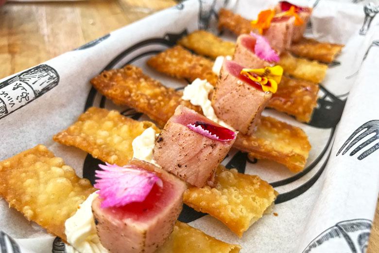Atum e Pastel (R$ 30). Porção de torradinhas de massa de pastel com atum marinado, sour cream e broto de coentro.
