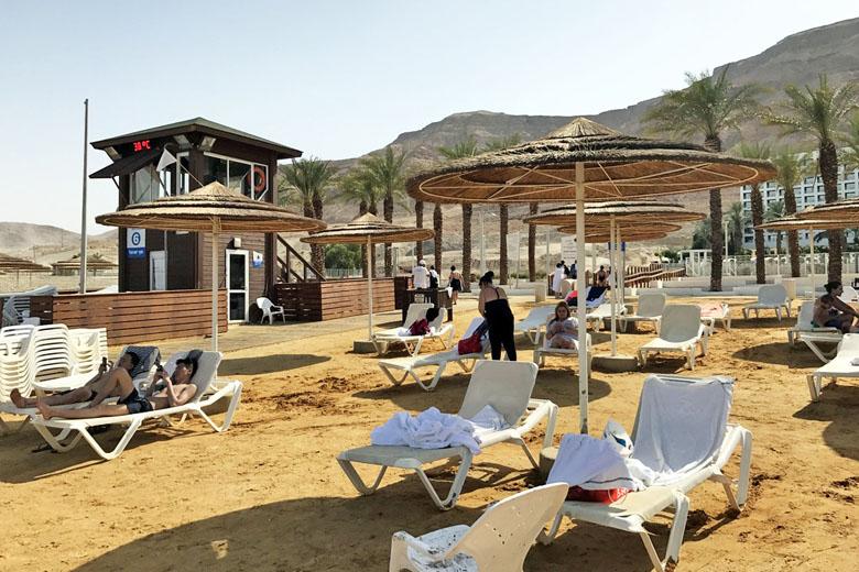 Praia de Ein Bokek: cadeiras, espreguiçadeiras, guarda-sóis e o posto salva-vidas.